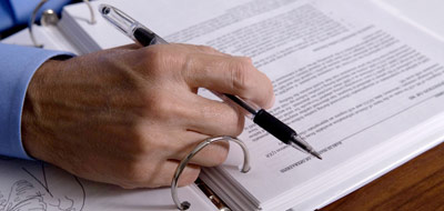 A hand holding a pen over a binder of documents