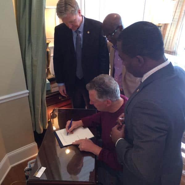 Governor Mcauliffe signs Neli Latson's pardon.