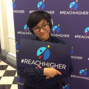 [A person named Elly Wong smiles and holds up a sign with the logo for the #ReachHigher campaign.]