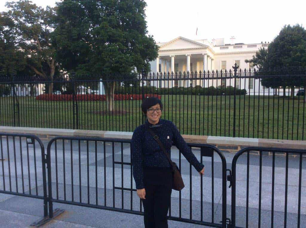 [A person named Elly Wong stands in front of the White House.]