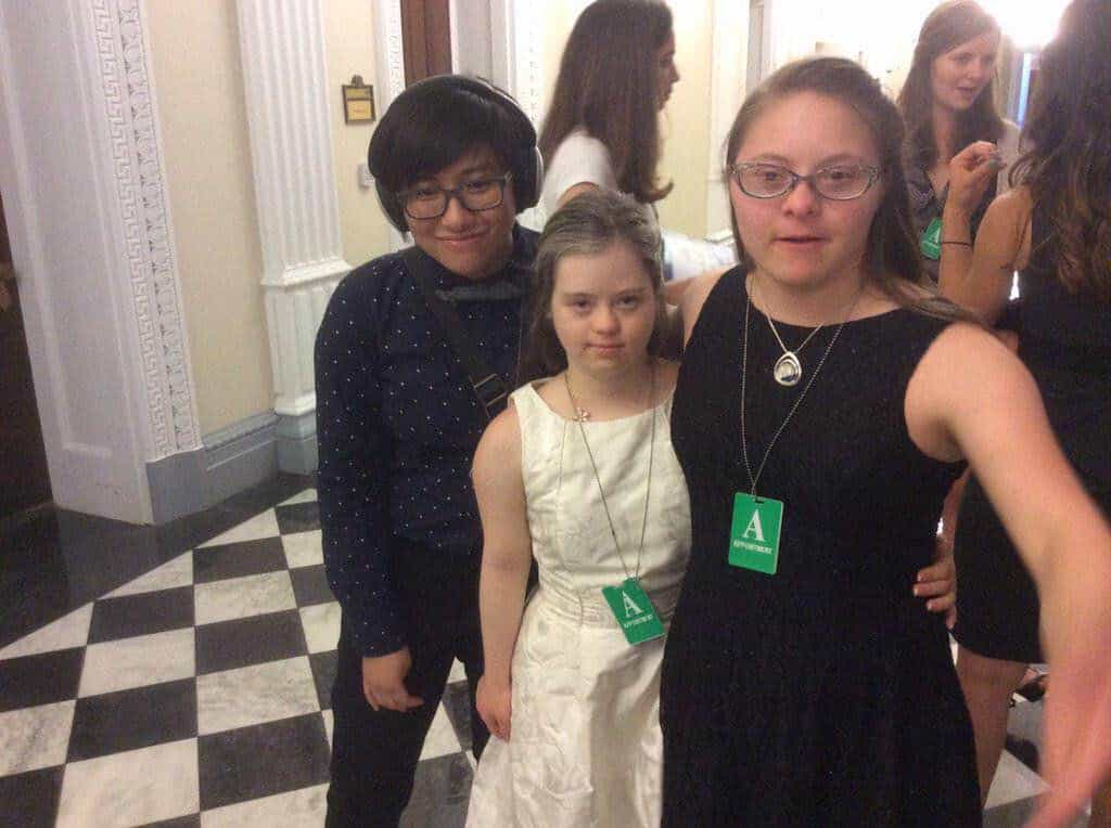 [Elly smiles and stands with Megan Bomgaars and Devon Adelman from the Global Down Syndrome Foundation.]