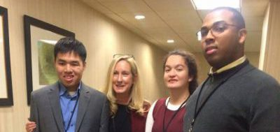 A young Asian man, a young white woman, and a young Black man are standing next to a white woman in her forties. They are in a hotel hallway.