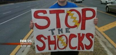 a person holding a sign that says Stop the Shocks