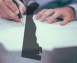 A person signing legislation with a silhouette of Delaware overlaid