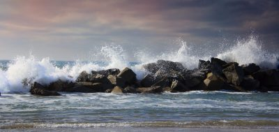 stormy ocean waves splashing high against rocks