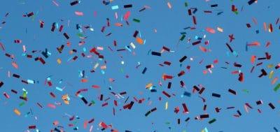 Multi-colored confetti against a blue background.