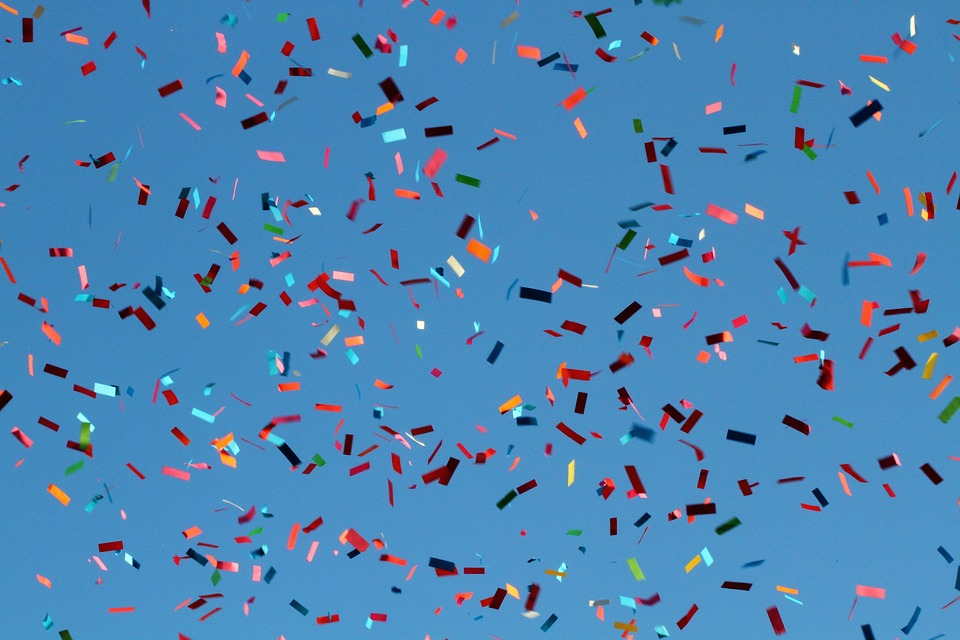 Multi-colored confetti against a blue background.