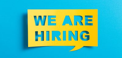 "A yellow speech bubble with blue text reading ""WE ARE HIRING"""