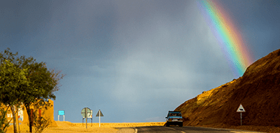 A rainbow emerges over a road after a storm