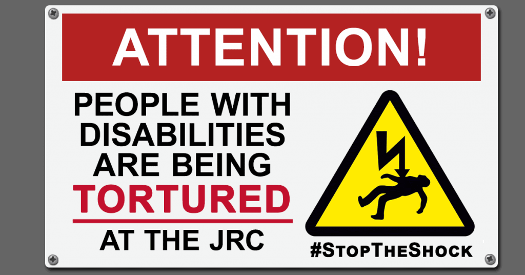 "[Image description: An illustration of a construction site-style metal warning sign. At the top, white text on a red background reads: ATTENTION! Below that is large text which reads: ""PEOPLE WITH DISABILITIES ARE BEING TORTURED AT THE JRC."" Next to the text is a warning symbol depicting a person being electrocuted against a yellow triangle background. Below the warning symbol is text reading #StopTheShock.]"