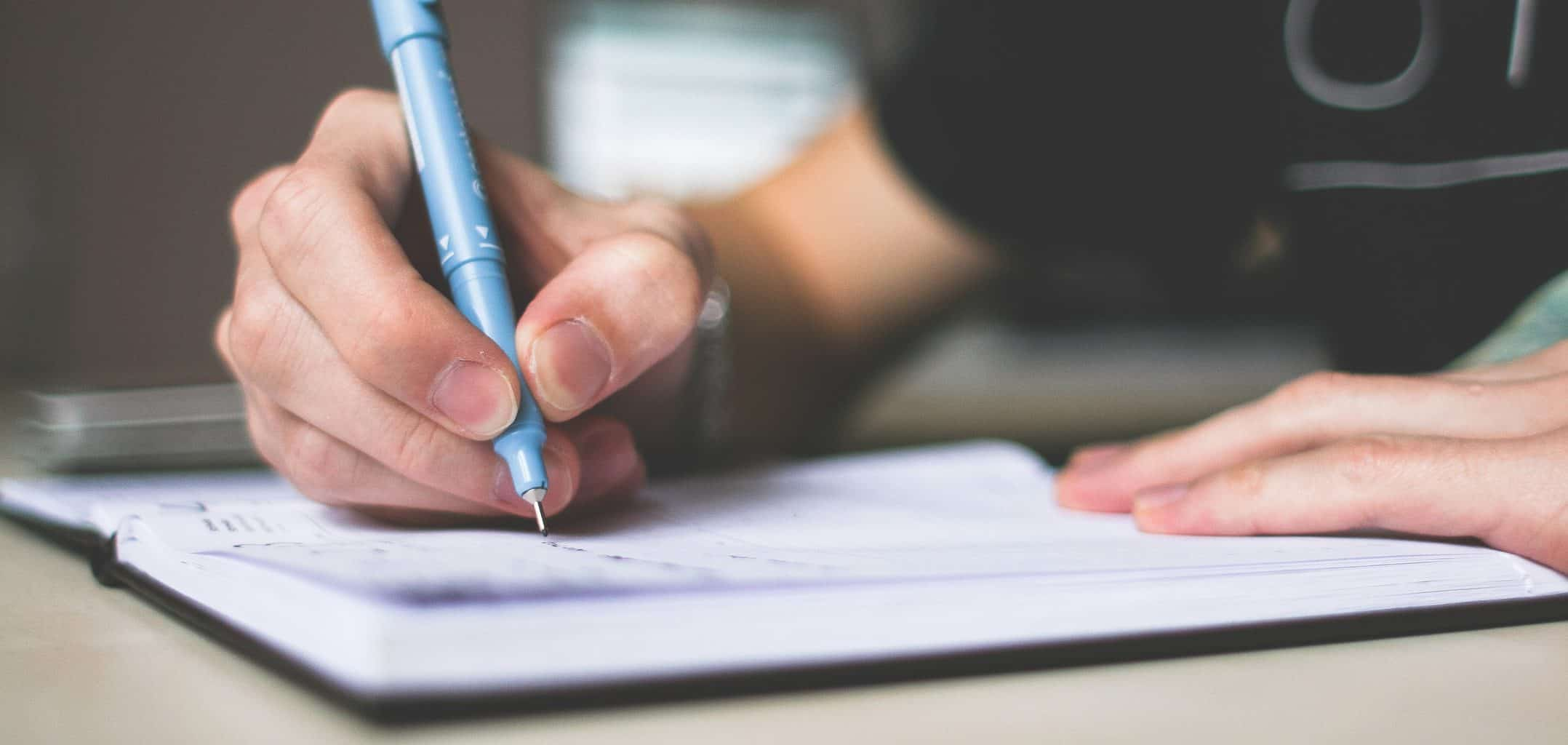 A person writing in a notebook with a blue ballpoint pen.