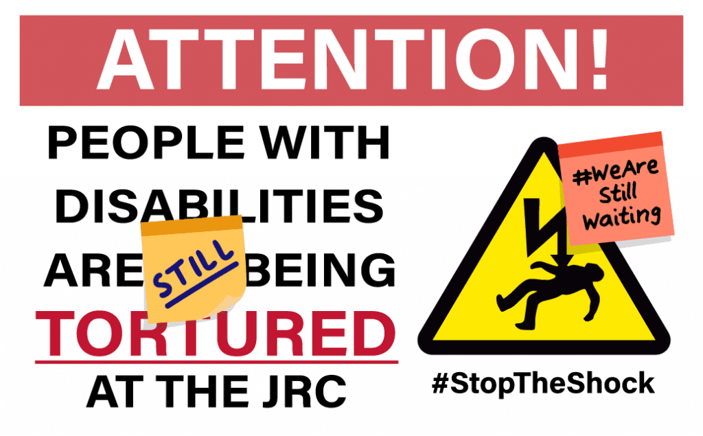 "An illustration of a construction site-style metal warning sign. At the top, white text on a red background reads: ATTENTION! Below that is large text which reads: ""PEOPLE WITH DISABILITIES ARE STILL BEING TORTURED AT THE JRC."" Next to the text is a warning symbol depicting a person being electrocuted against a yellow triangle background. Below the warning symbol is text reading #StopTheShock. There is a post-it note on the sign that says #WeAreStillWaiting."