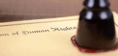 """a wax stamp being placed on a parchment that says """"declaration of human rights"""""""