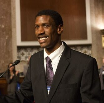 A smiling Black man dressed in a suit and tie stands at a podium delivering a speech with several people in the background