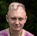 A young white person stands against a dark background, smiling at the camera. They have dyed blond hair that is shaved on the sides. They are wearing a purple shirt and have several necklaces hanging around their neck.